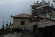 На левом углу крыши дома сидит та самая обезьянка. Видите?