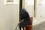 Португалия.Эвора.Пожилая женщина у своего дома моет тротуар.