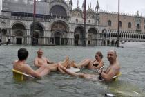 Туристы купаются в центре Венеции во время наводнения