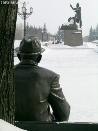 Ветеран сидит как раз напротив памятника танкистам.