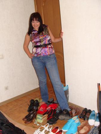 Люда на примерке на открывшейся у нее в коридорчике распродаже модной сезонной обуви.