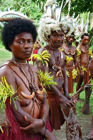Маданг. В гостях у племени. Встречали нас папуасы в праздничных нарядах: набедренных повязках из специальных растений, голова украшена перьями, на шее бусы из ракушек, зубов собак и клыков кабана. На лицах -  «макияж» из красной глины.