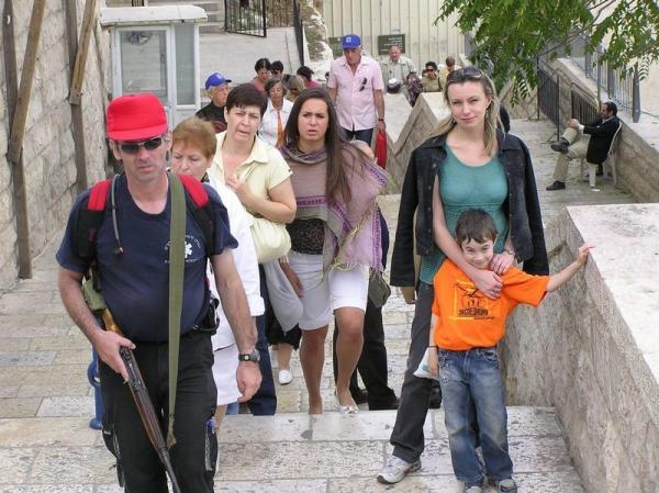 Человек с ружьем - обычная картинка на улицах Израиля. Этот в исторической части Иерусалима сопровождает туристов.
