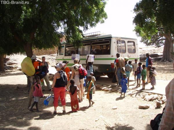 Приехали в деревушку Дуру. Дети мгновенно погрузили на головы 18-килограммовые ящики с водой и бодро потопали в деревню.