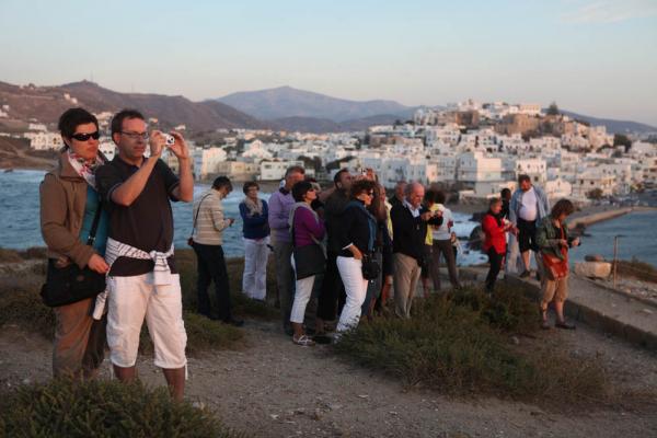 туристы, пытающие снять закат через арку